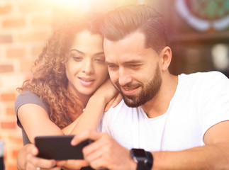 Happy couple using a smartphone sitting in terrace