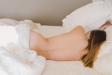 Naked back view woman sleeping in bed
