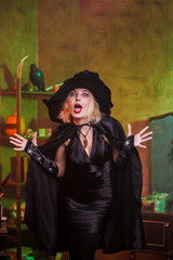 Photo of screaming witch in black hat, dress on background of rack with pumpkin and crow