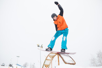 Picture of young sporty man with his hand raised skiing on snowboard