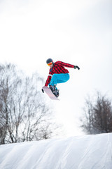 Photo of athlete in helmet riding snowboard from snow slope