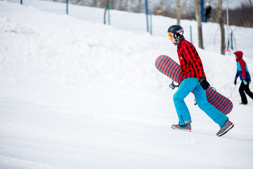 Image of sporty man with snowboard walking on snowy resort