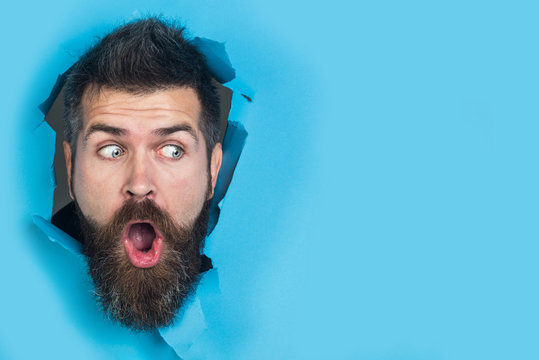 View of male face through hole in blue paper. Surprised bearded man making hole in paper. Copy space for advertising, to insert text or slogan. Discount, sale, season sales.