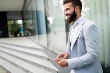 Shot of smiling businessman sitting on bench with digital tablet