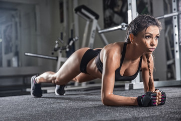 Attractive young woman is doing plank exercise while working out in gym Wall mural