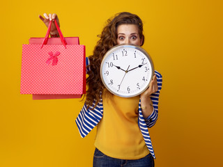 surprised woman hiding behind clock and showing shopping bags