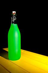 Neon green bottle on yellow table. Painterly fantasy still life