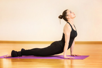 Young woman is training yoga in svanasana pose at gym.