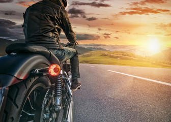 Motorcycle rider ready for drive in Alps, beautiful sunset sky