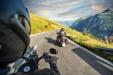 POV of motorbiker holding steering bar, riding in Alps