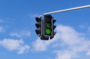 Traffic light with green light signal on sky background