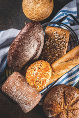 Variety of fresh homemade grain bread, in a metal basket, dark rusty background copy space top view