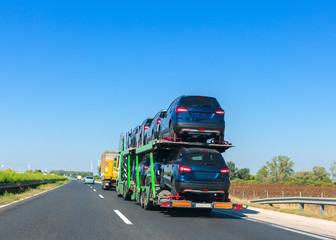 Car carrier trailer with cars on bunk platform. Car transport truck on the highway. Space for text