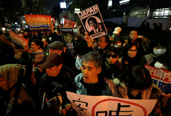 Protesters shout slogans and hold placards during a rally denouncing Japanese Prime Minister Shinzo Abe and Finance Minister Taro Aso in Tokyo