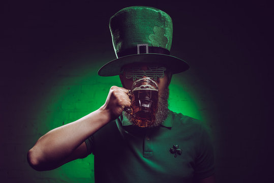young bearded man in green irish hat drinking beer