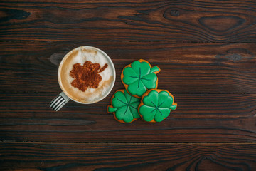 top view of cappuccino and cookies in shape of shamrocks on wooden table