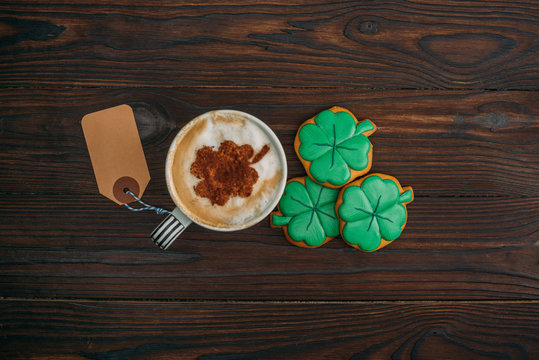 top view of cup of coffee with blank label and cookies in shape of clovers on wooden table