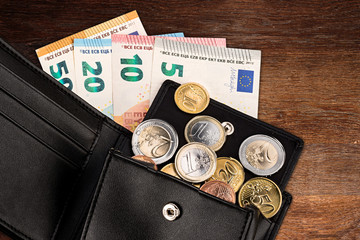 euro coin and bank note in black leather wallet on wood wooden business finance background