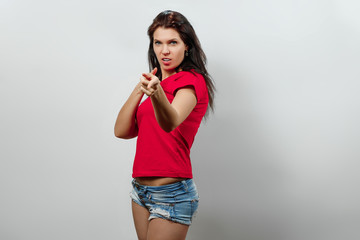 A young, beautiful girl shows a gesture with her gun. Isolated on a light background. Different human emotions, feelings of facial expression, attitude, perception, body language, reaction.