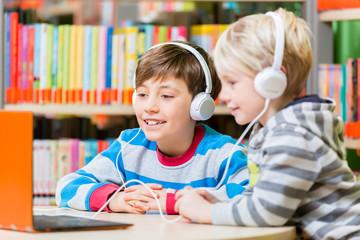 Kinder in der Bibliothek hören sich Hörbücher an mit dem Kopfhörer