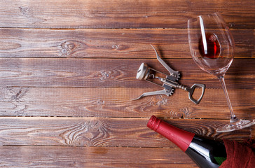 Photo of bottle of wine, corkscrew, wine glass on brown, wooden background.