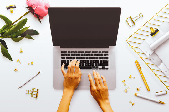 A feminine desktop flatlay scene, with a laptop, female hands, a pink peony, gold tray and other gold stationery accessories. On a plain white desk background.