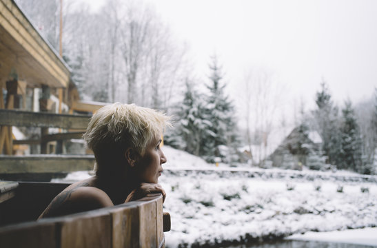 Side view of woman swimming in plunge tub in winter