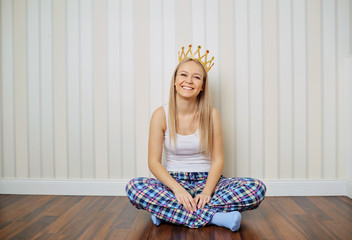 Funny blonde girl in pajamas with crown on her head smiling sits on the floor against a striped wall background. Young woman princess laughs in the room.