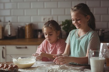 Siblings preparing cupcake in kitchen