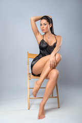 Woman posing in the black lingerie on the chair