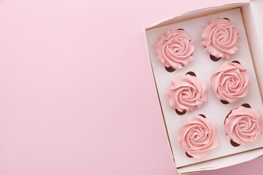 Muffins or cupcakes with flower shaped cream in box on pink background, top view