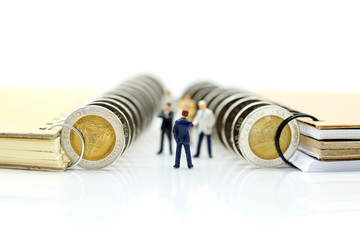 Miniature people : Businessman stand with coins of book,education or business concept.
