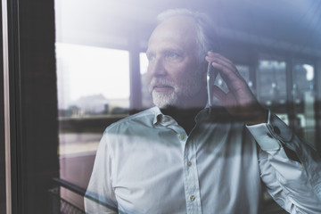 Portrait of mature businessman at the window talking on cell phone