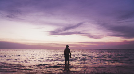 Thailand, Phuket, silhouette of man wearing hat wading at seafront by sunset