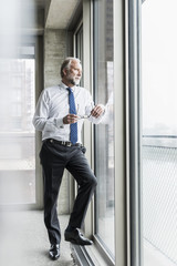 Serious mature businessman standing at the window looking out