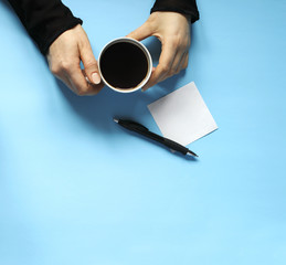 Woman holding coffee mug in hand on blue background, top vew, copy space