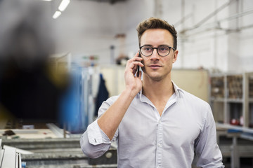 Young businessman on cell phone in factory Fototapete