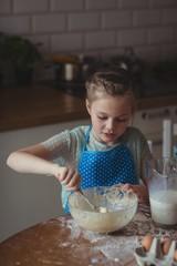 Little girl preparing cookies in kitchen