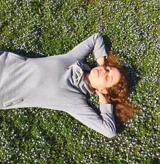 una ragazza sdraiata sul prato di fiori primavera