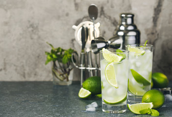 Mojito cocktail with lime and mint in glass on a stone table. Bar tools and ingredients for cocktail.