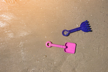 beach toys  spade and shovel on sand, beach background