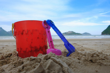 beach toys  buckets, spade and shovel on sand, beach background