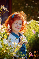 Closeup beautiful portrait ginger curly little girl in the blossoming flower garden