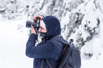 a man in a snowy winter forest with a backpack and a camera