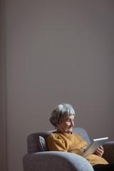 Senior woman using digital tablet in living room