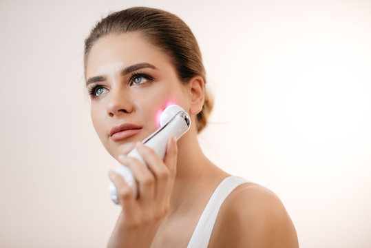Young healthy fresh woman with natural make-up using the electric facial massager at isolated white background.