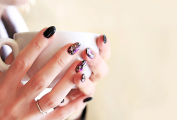 woman hands with beautiful manicure holding a cup of coffee - black polish with designed fashion shapes