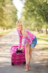 Beautiful cheerful young blonde women going on vacation. Happy female traveler dragging packed suitcase along the road