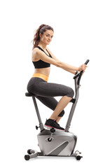 Fitness woman riding an exercise bike and looking at the camera