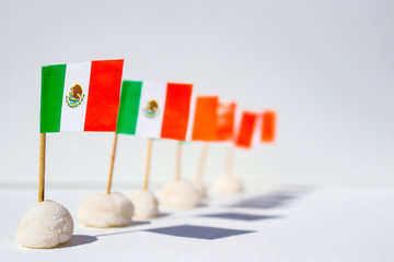 Row of mini Mexican flags in a row with interesting shadows - shallow depth of field with front one in sharp focu against white background